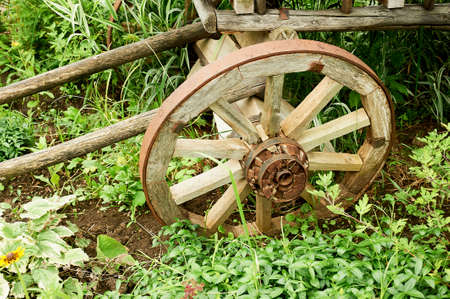 An old wooden wheel. Part of the cart. An ancient means of movement, with the help of horses.