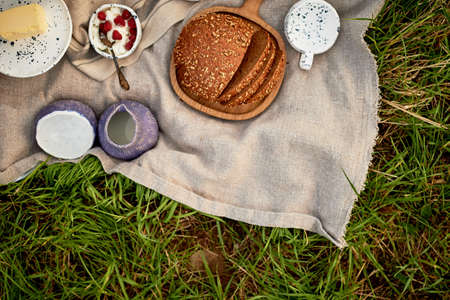Picnic in nature. Fresh bread with cereals on a wooden board, linen tablecloth, pottery. Eco-style. Standard-Bild