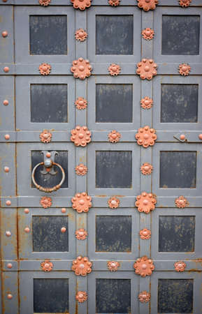 A metal door with a round handle. An old door decorated with forged elements.
