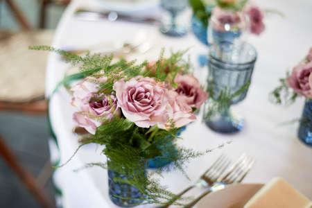 Powder roses in small blue vases. Wedding decor or romantic date design. Floristics.