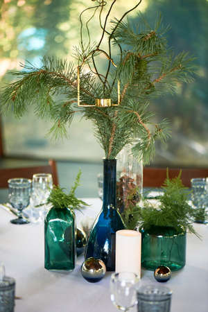 Restaurant design. A table covered with a white tablecloth, a classic serving. Bottles of blue and green glass. Paws ate.