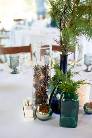 The decor of the table in the restaurant. Bottles of green and blue glass, mirror balls and spruce paws.