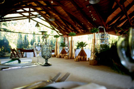 Banquet hall in the open air with a wooden ceiling, hanging garlands. Eco design.