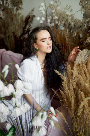 Girl with long dark wavy hair, natural thick eyebrows. In a white cotton dress.Among cereals and flowers. Touches the plant with her fingers. Tenderness and lightness. Standard-Bild