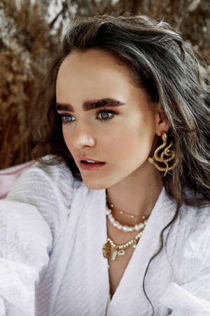 Portrait of a beautiful girl with wavy long hair, dressed in a white cotton dress with wide sleeves. Natural thick eyebrows, gold jewelry.