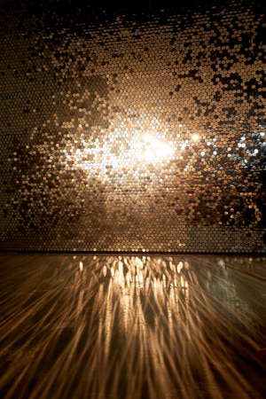 A wall with gold sequins, glare on the floor. Empty space, glamorous chic