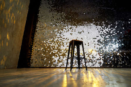 High stool on a metal base against the background of the wall with sequins. The glare is reflected on the floor. Glamorous design. Standard-Bild