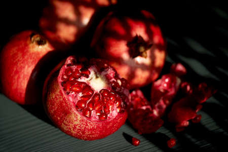 Pomegranate on a black background. Shadow from the suns window. Whole and seeds. Vitamins in hot climates.