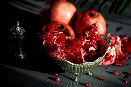 Broken juicy pomegranate in a metal vase on the legs. Oriental flavor.