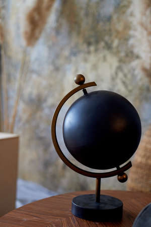 Black decorative globe. The subject of the interior in the style of minimalism. An interesting solution for home and office Standard-Bild