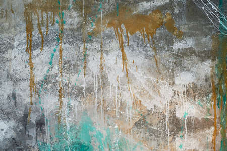 The wall with flowing gold and turquoise paint, the main tone is gray. Texture with a place for text. Standard-Bild