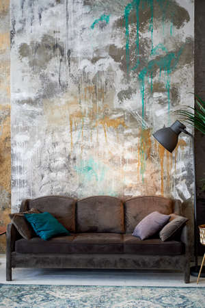 A dark chocolate-colored sofa against a multi-colored textured wall. A black floor lamp. The design of the room.