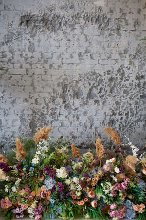 Composition of flowers against the background of a gray wall. Floristics in the design of the room. Dry flowers.