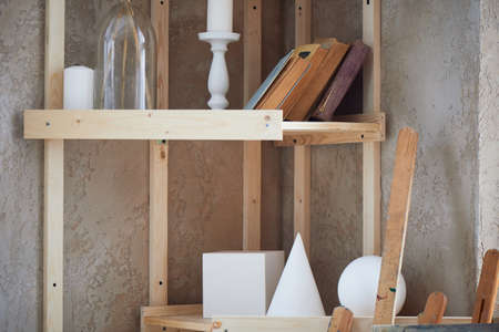 Shelving in a creative workshop.Plaster shapes of different shapes, candles and books