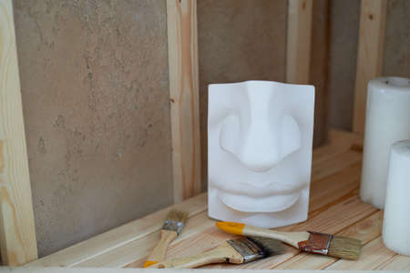 Shelving in the artists studio. Plaster face for sample, brush and candle. Creative atmosphere.