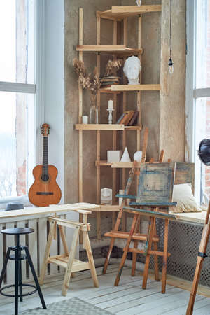 The artists light workshop with large light windows. An old big lamp on a tripod. Shelving with plaster forms, easels Standard-Bild
