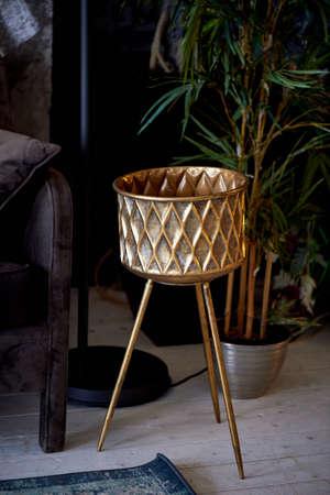 A gold vase on a tripod. Decoration of the dark interior. Room design Standard-Bild