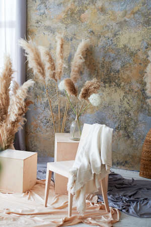 Light interior with wooden chair, cubes and draped fabric. A creative workshop. Decor with dry pampas