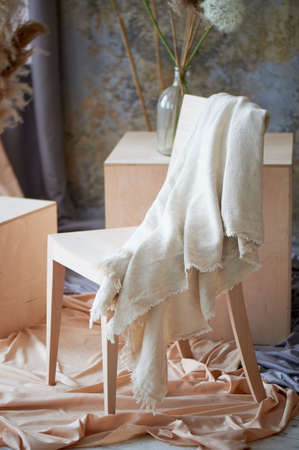Light interior with wooden chair, cubes and draped fabric. A creative workshop