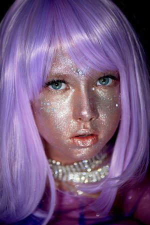 A little girl in a purple wig with silver sequins on her face. An alien, fantasy world.A fairy or an alien.