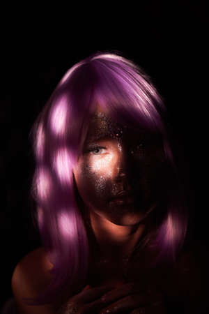 Fantastic portrait of a little girl in the world of fairies. Glitter, spots of light on her face.