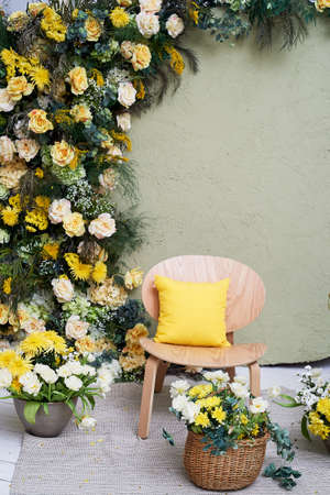Spring decoration or photo zone. A garland of flowers. chair. Baskets with yellow flowers. Interior design and floristry.