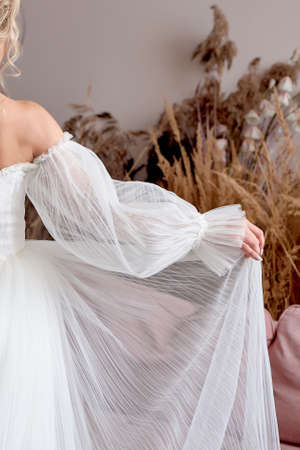 The bride in a white long dress. How the princess holds the hem of the dress. The morning of the bride.