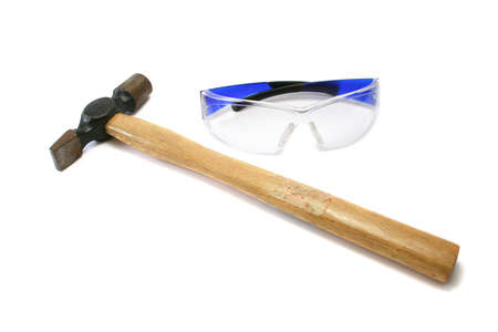 and worn out: hammer and safety glasses. Hammer has an old warning sticker but its message has been lost with use. Stock Photo