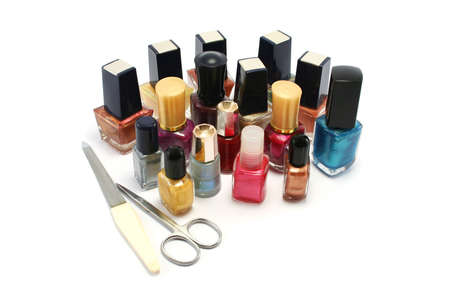 a wide selection of coloured nail varnishpolishes with a small scissors and metal nail file photo