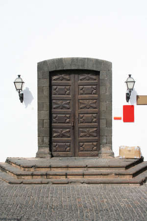 Beautifully carved wooden doors to a monastry, now a museum. Shaped lava rock surround and an old cardboard box of stuff on the doorstep! photo