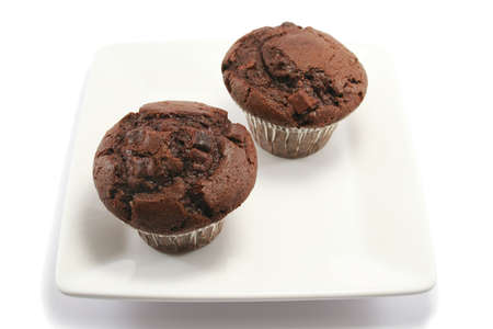 choc: two delicious chocolate chip muffins on a square china plate Stock Photo