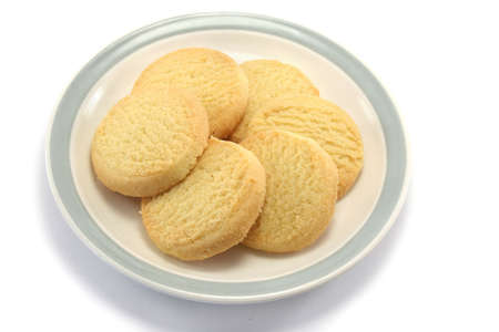 fairly: six tasty round shortbread biscuits on a teaplate, taken from a fairly high point of view
