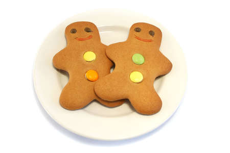 Two Gingerbread men on a cream plate on a white background photo