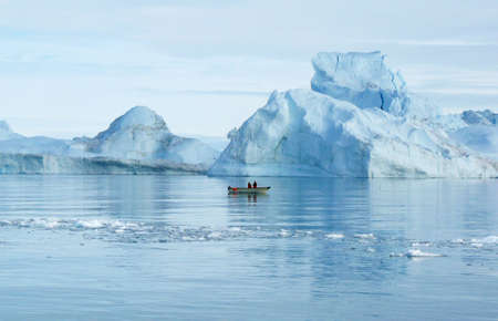 harsh: two men in a small boat, checking their catch in the shadow of the icebergs
