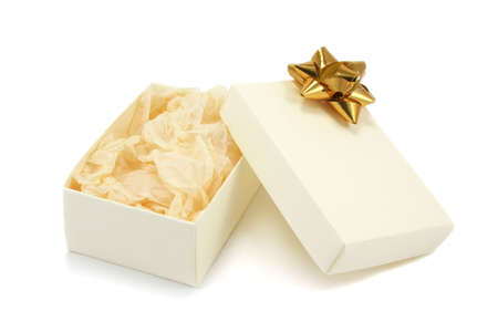 present presentation: A open cream textured cardboard gift box with a gold metallic bow and crumpled tissue paper on a white background