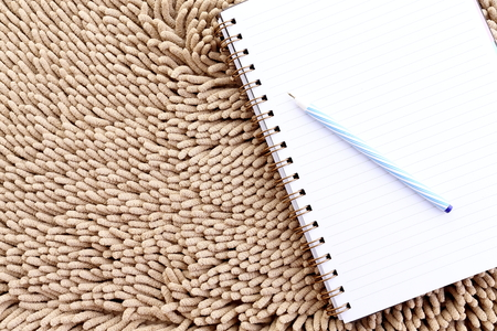 Notepad with pen on carpet photo