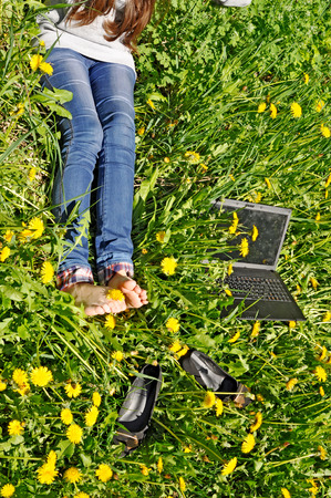 legs and notebook lying on herb with yellow dandelion Stock Photo - 76995036