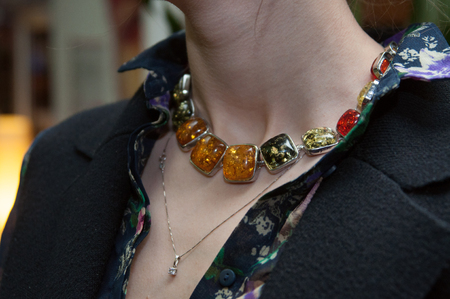 necklace made of amber and other red glass beads on the neck of the girl Stock Photo