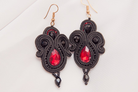black earrings with red glass on white background
