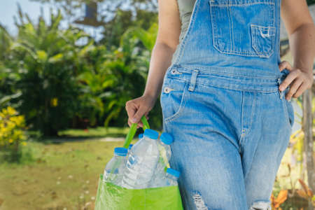 Plastic collection, environmental protection. Transparent plastic bottles in a bag. Female hand with a full bag for recycling on a background of tropical greenery. Stock fotó