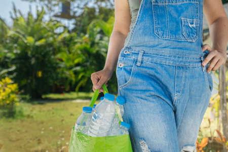 Recolección de plástico, protección del medio ambiente. Botellas de plástico transparente en una bolsa. Mano femenina con una bolsa llena para reciclar sobre un fondo de vegetación tropical. Foto de archivo