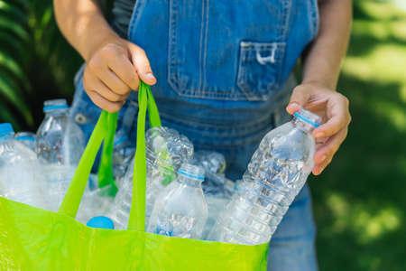 Recolección de plástico, protección del medio ambiente. Las manos de la mujer recogen las botellas y las ponen en una bolsa verde reutilizable.