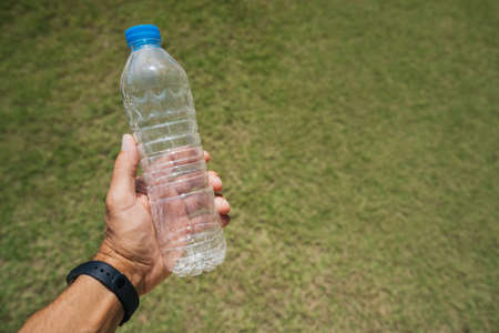 A man holds in his hand an empty plastic bottle on a background of green grass. Plastic problem and failure. Photo series.