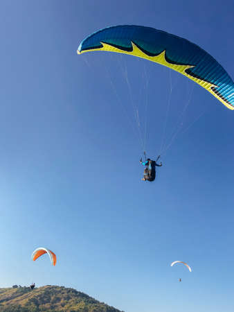Paragliding. Skydivers in the blue sky. Coast and Adrenaline.
