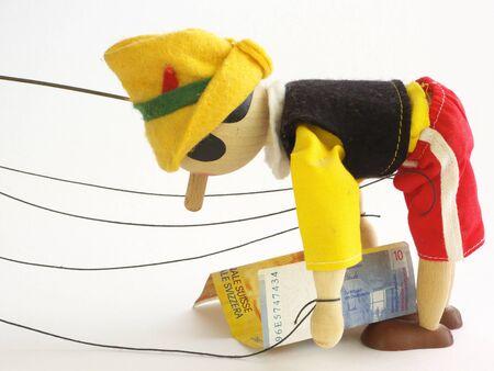 marioneta de madera: Plantea billetes de t�teres de madera en 10 francos suizos. Aislado.  Foto de archivo