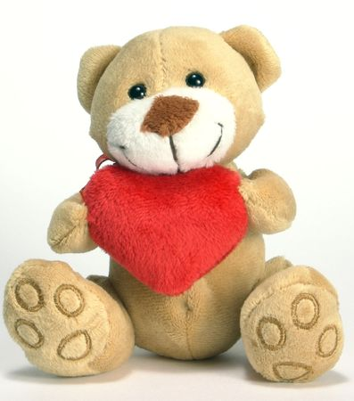 homogeneous: Soft toy - bear. In claws keeps heart. The gift of Valentine `s Day. At a homogeneous background.