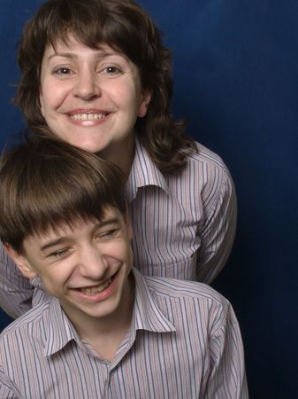 gaily: Young mother and her adolescent son. They laugh. They wear the same shirt. Stock Photo