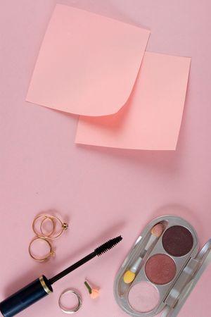 posting: Cosm�ticos y papel. Al fondo de color rosa. El modelo para la publicaci�n de sus im�genes o inscripciones.