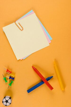 posting: Notes, crayons, pins, eraser - to orange paper. A design to accommodate your photo or inscriptions.