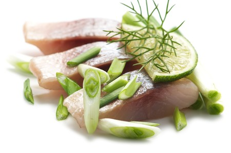 Pieces of herring with lime and green onion isolated on a white background.